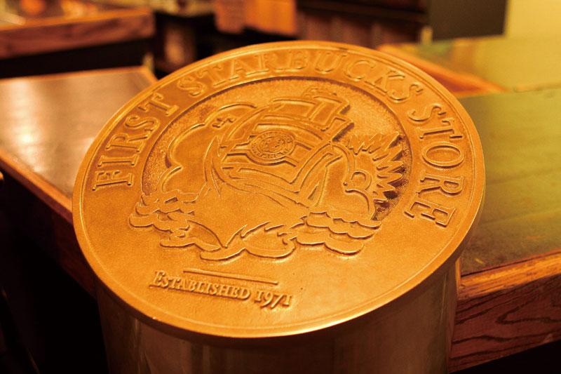 スタバ1号店内のカウンターにある真鋳のロゴマーク。