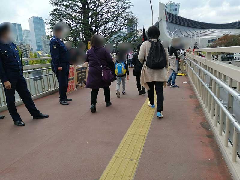 歩道橋で開催反対の人たちがアピール